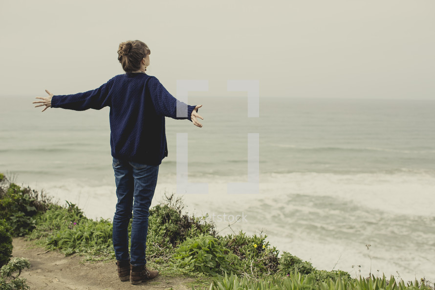 woman standing out on a ledge looking out over the ocean with her arms spread