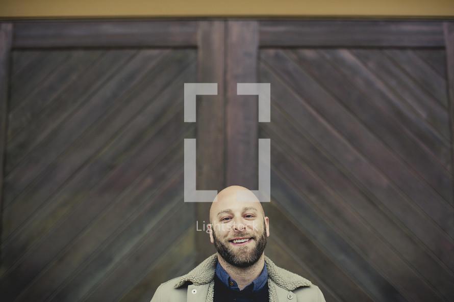 smiling man standing in front of wood doors