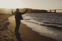 man standing on a beach in front of the ocean with his hands raised in praise