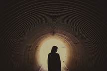 silhouette of woman standing in a tunnel