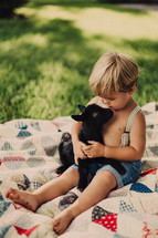 a bare chested toddler boy in suspenders hugging a goat