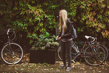 blonde woman standing next to a bicycle