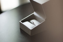 A plain wedding band in a ring box.