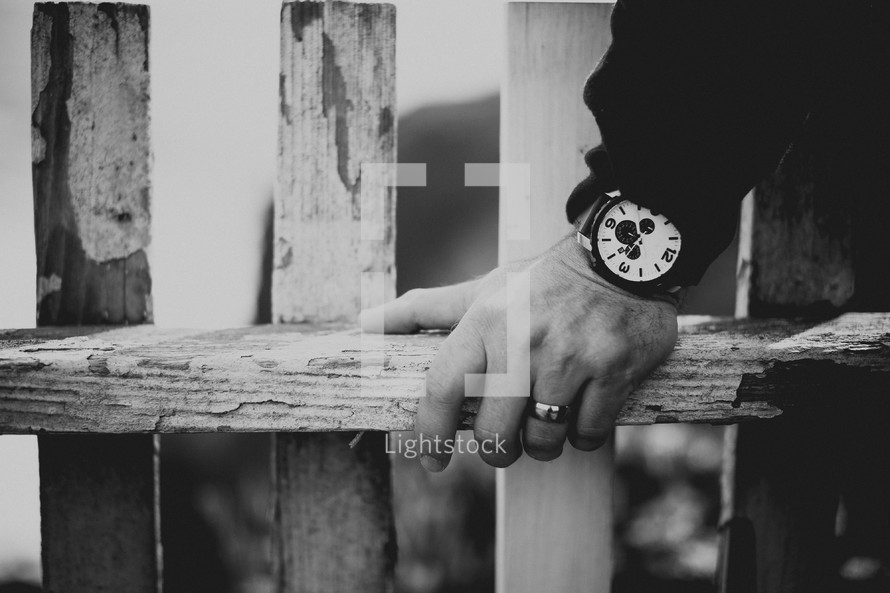 Man's hand leaning on wooden fence railing.