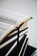 An open Bible on top of a stack of hardback books.