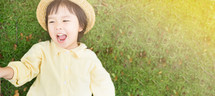 little girl in a straw hat and yellow coat