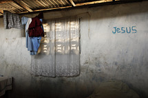 Hut with clothes hanging and Jesus written on the wall