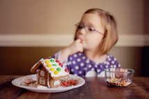 a child decorating and tasting a gingerbread house