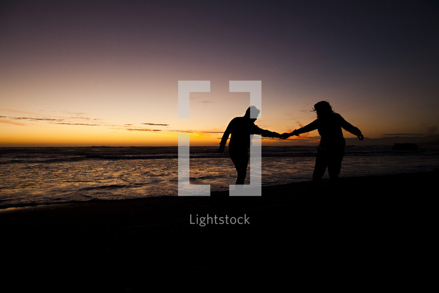 silhouette of a couple walking holding hands on a beach at sunset relationship engagement marriage love man woman