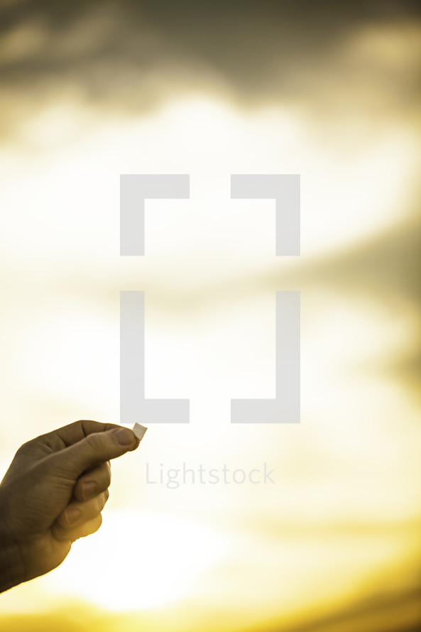 outside communion - hand holding a piece of bread