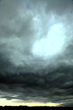 Stormy sky and clouds over hillside horizon.