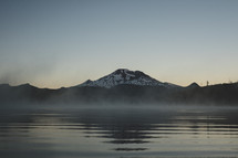 Early morning misty lake with a mountain in the background | Ripples of water | Peaceful | Dawn