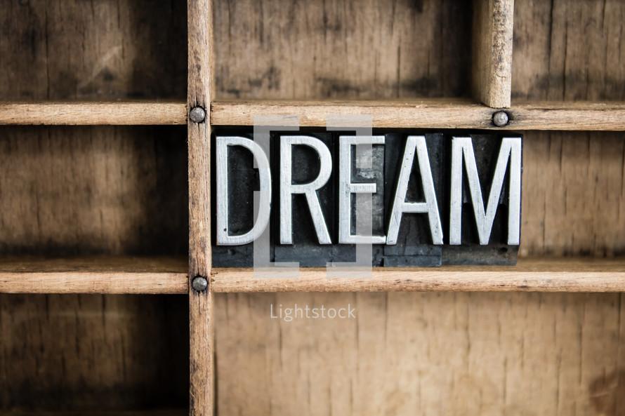 word dream in blocks on a bookshelf