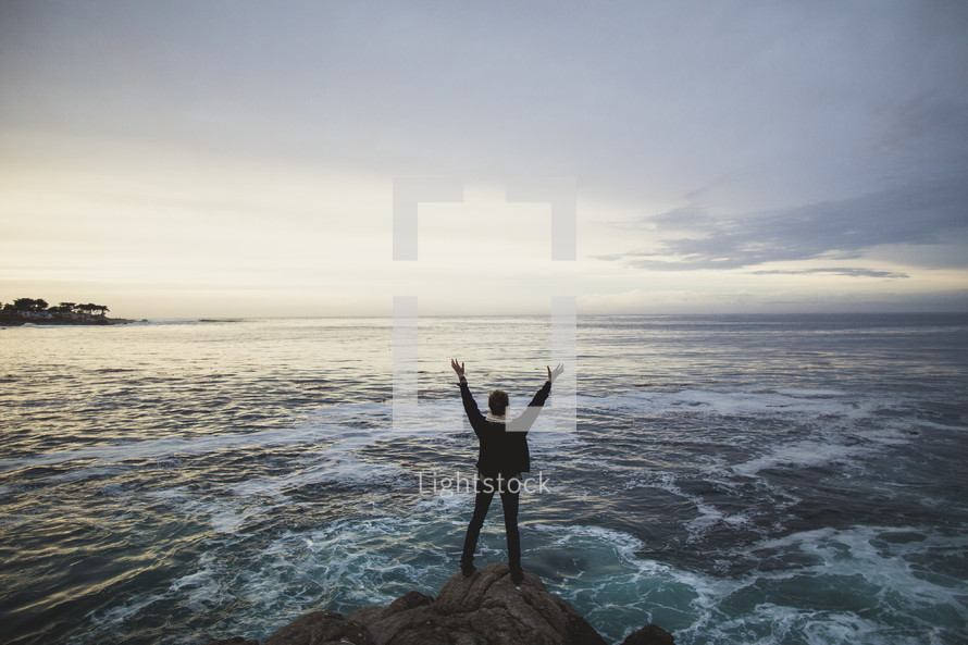 woman standing on a rock looking out over the ocean with her arms raised