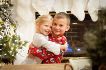 brother and sister hugging at Christmas