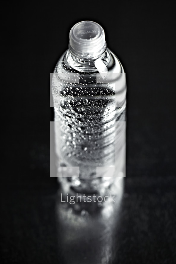 A refreshing bottle of water on seamless black