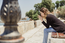 woman saying a prayer sitting on a bench in Greece