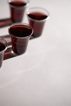 A few communion cups filled with wine isolated on white.