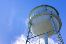 Low angle view of a water tower with clouds and blue sky in the background.