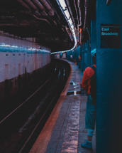 man standing in a subway tunnel