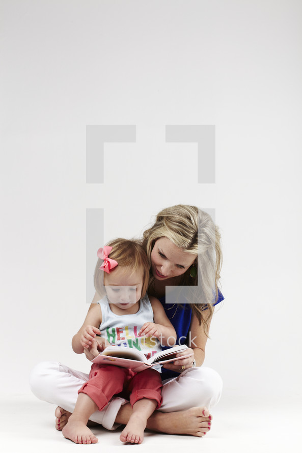 A mother reading the bible to her daughter on her lap