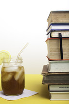 stack of books and glass of iced tea