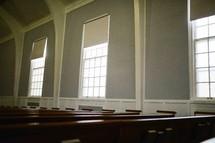rows of church pews in an empty church