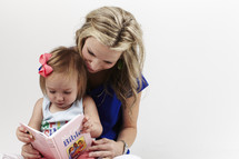 mother reading a children's bible to her toddler daughter