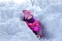 a toddler girl in a snow drift
