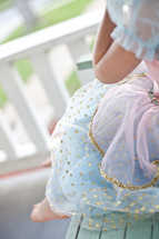 Girl in a princess dress sitting on a wooden porch swing.