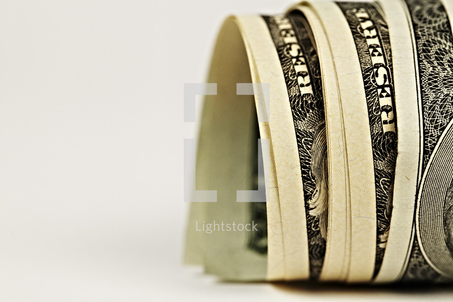 Dollar bills rolled together isolated on white