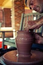 A potter molding a clay pot