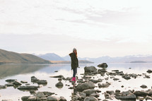 A girl stands on rocks at a lake's edge.