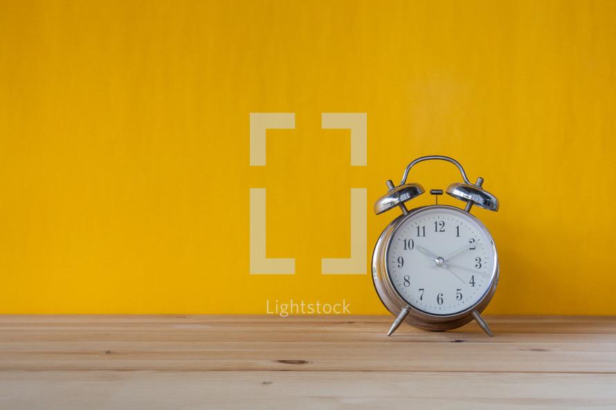 alarm clock on a wood desk