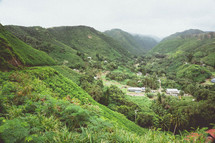 green mountains and homes in a valley