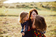 a mother kissing her daughters