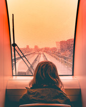 child looking out a train window