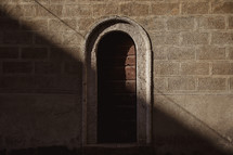 arched wooden door on the side of a church building in Italy
