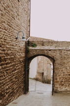 an archway leading to a narrow street