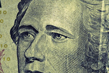 A close up view of Alexander Hamilton on a ten dollar bill
