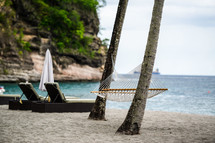 A hammock between palm trees on a beach by the sea.