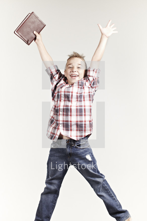 A boy jumping with a bible in his hand