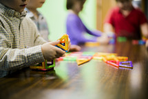 children playing with magnetic toys on a wood table