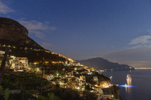 homes along a mountainous coastline in Italy at night