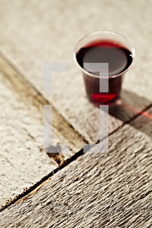 A communion cup filled with wine sits on a wooden table