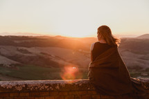 a woman sitting on a wall looking out at the view at sunset in Italy