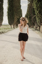 a woman standing in the middle of a gravel road in Italy
