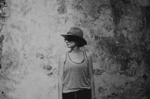 a woman in a hat and tank top standing in front of a grungy wall