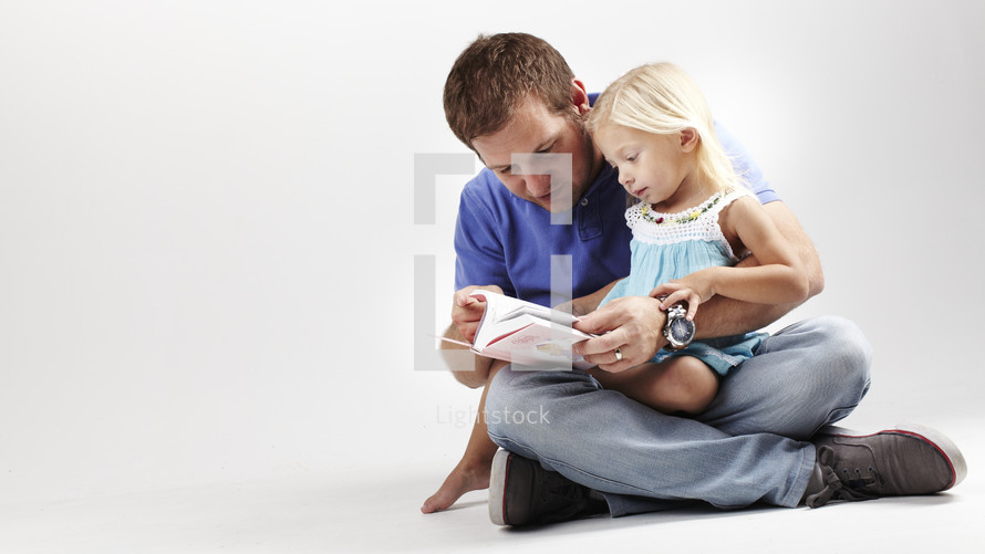 A dad reads a Bible with his young daughter in his lap.
