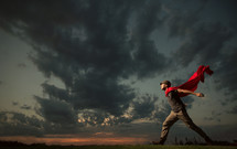 man wearing a red scarf running under cloudy skies